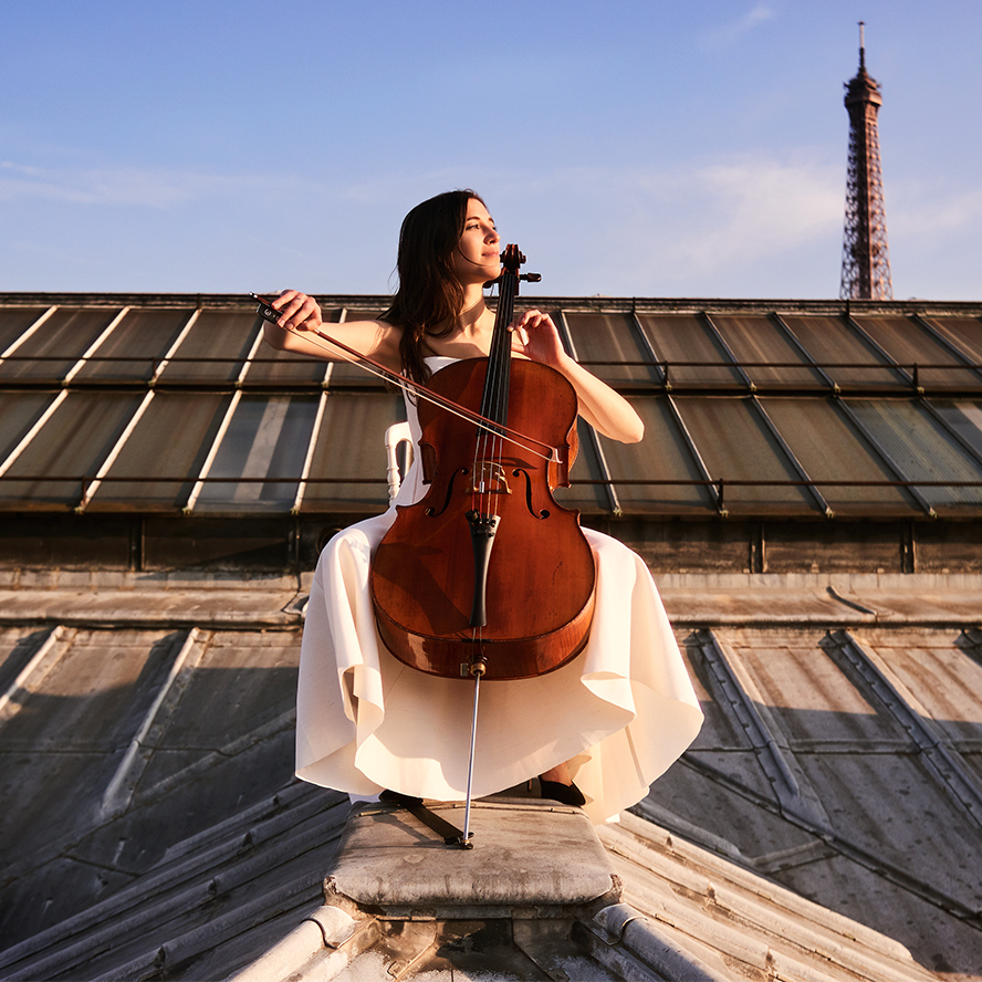 Camille Thomas with cello on top of a building